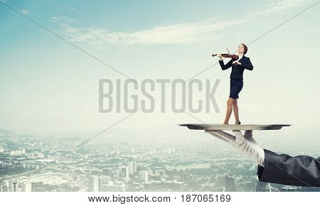 Hand of waiter presenting on tray woman playing violin
