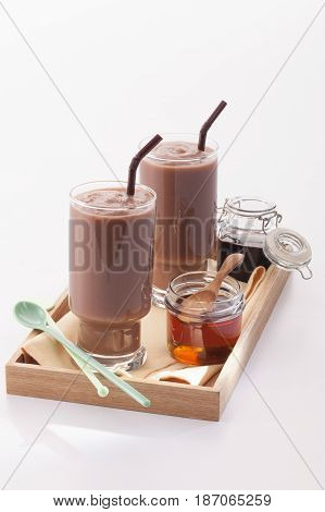 Double cocoa frappe with syrup on wood tray isolate background