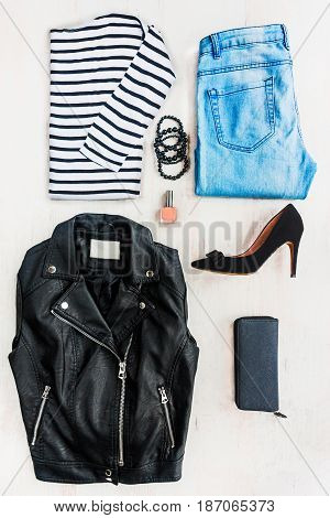 Collage of female clothing set. Blue jeans striped blouse leather jacket black high heels shoes and accessories over white wood background.