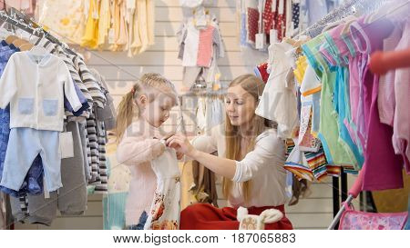 Portrait of mother with her daughter, who was trying a dress in a children's store.