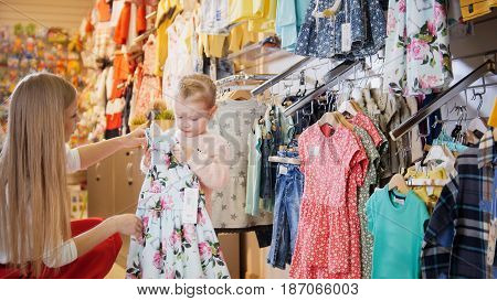 Portrait of a young woman and a little girl. Mother and daughter in a children's store considering blue summer dress with large pink flowers.