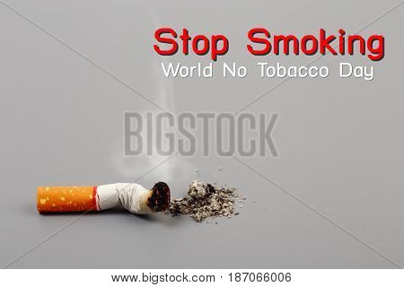 World No Tobacco Day Cigarette is burning with smoke on gray background.