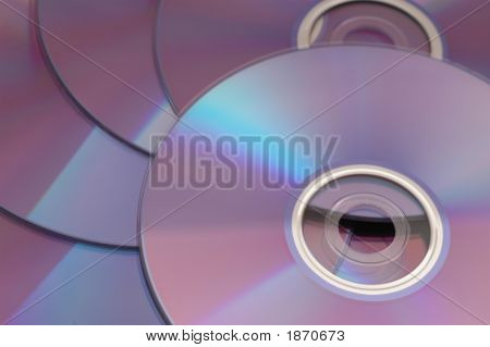 Cds / Dvds Stacked On Top Of Each Other Reflecting Light Spectrum