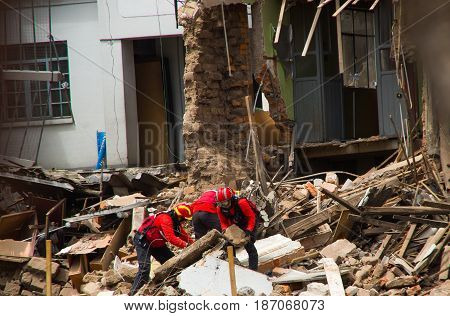 Quito, Ecuador - December 09, 2016: An unidentified group of firemans, cleaning the damage building in Quity Ccity