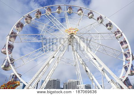 close up white ferris wheel with cloudy blue sky taken at Darling Harbour in Sydney Australia on 6 July 2016