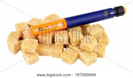Diabetic insulin syringe pen on top of sugar cubes isolated on a white background