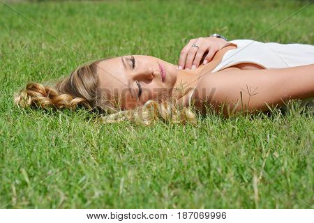 Girl laying in the grass in a white dress