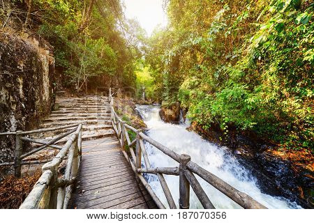 Wooden Boardwalk And Stone Stairs Leading Along Mountain River