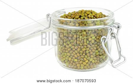 Glass food storage jar filled with green lentils isolated on a white background