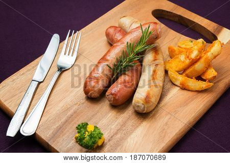 Grilled assorted sausages with fried potato wedges