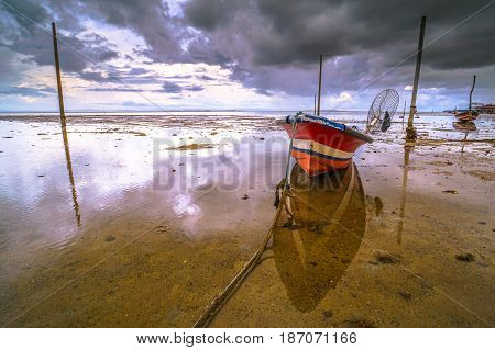 Fishing boat against colorful sky with clouds and low tide beach at sunset in Labuan island,Malaysia.