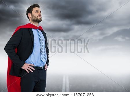 Digital composite of Business man superhero with hands on hips against road and grey sky with flare