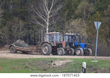 Two tractors at countryside - machinery for agriculture, telephoto