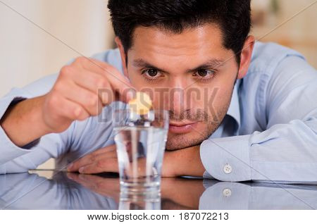 Handsome man dropping effervescent tablet in glass of water.