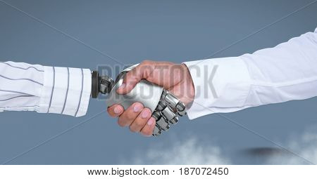 Digital composite of  Robot hand shaking businessman hand with blue background