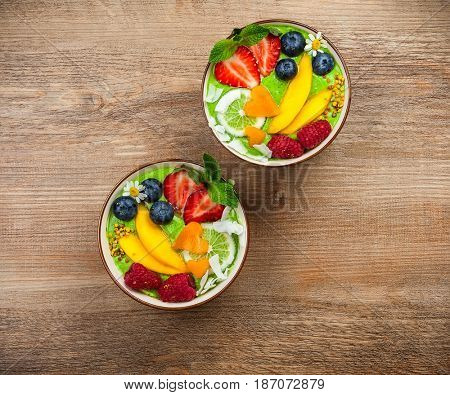 Green Smoothie in bowls for healthy breakfast. Fresh organic smoothie made from spinach, banana, spirulina,wheatgrass and lime with berries and fruits on wooden background.Top view, copy space