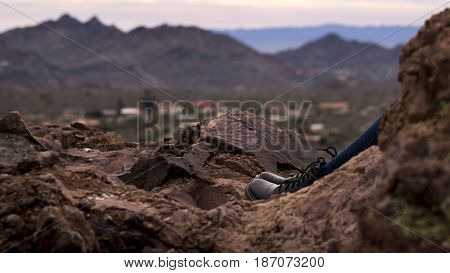 Scenic boots with dark jeans peaking out from behind a rock with the view of Phoenix Arizona mountains and houses in the background