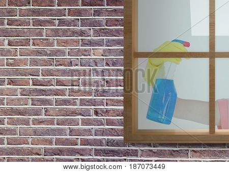 Digital composite of hand cleaning the window of the bricks house