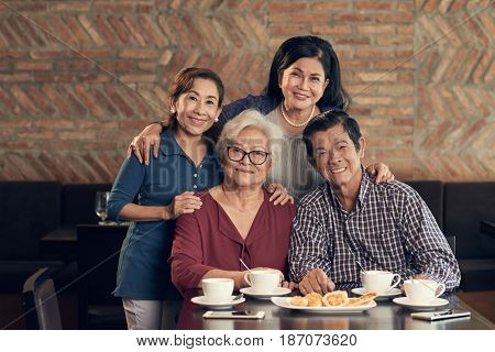 Group of Vietnamese senior people hugging and looking at camera