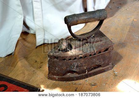 Old cast-iron iron on the floor of the dark loft