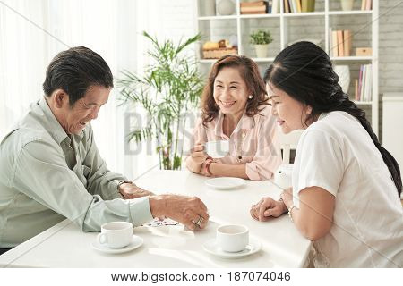 Cheerful senior people drinking tea and playing cards at home