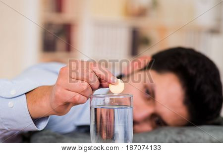 Handsome bored man holding a pill effervescent tablet in his hand ready to drop in a glass of water.
