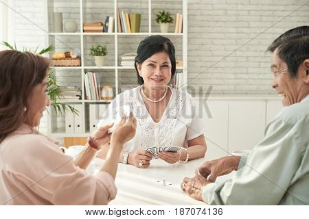 Pretty senior Asian woman playing cards with her friends
