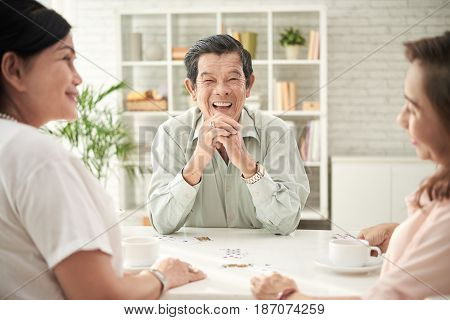Laughing senior man spending time with friends at home