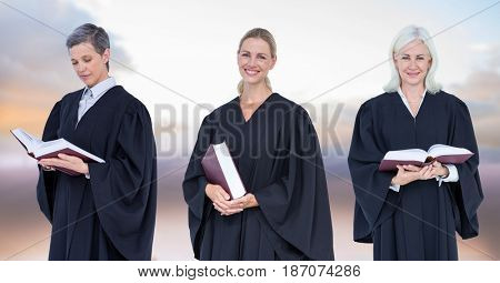 Digital composite of Women Judges holding books in front of sky clouds