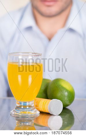 Handsome guy behind of Lemon, pills of vitamin C and a glass of vitamin C dissolved over the table.