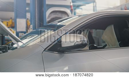 Lifted car in auto workshop - small business, close up