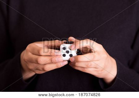 Quito, Ecuador - February 10, 2017: Fidget Cube stress reliever manipulated with both hands.