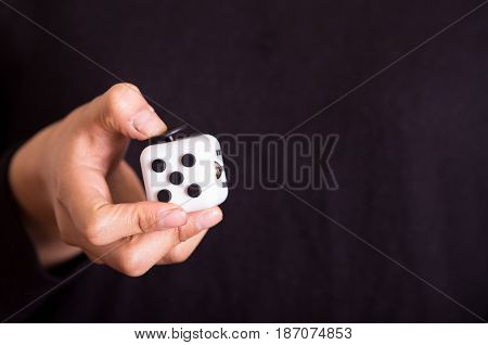 Quito, Ecuador - February 10, 2017: Man holding a Fidget Cube stress reliever, in black background.