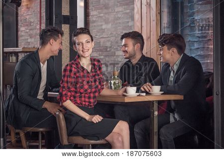 young adults coffee shop table small group of people talking sitting in bar stool happy smiling woman looking to the camera
