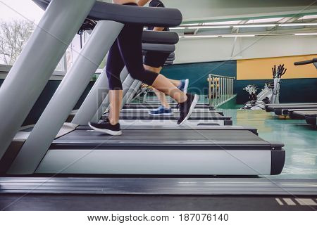 Close up of people legs running over treadmill in a training session on fitness center