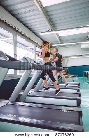 People running over treadmill in a training session on fitness center