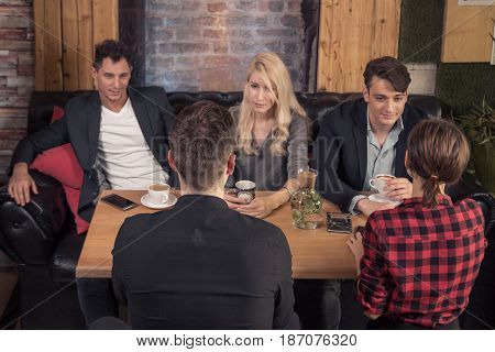 five people small group of people talking young adults sitting sofa coffee shop table indoors looking at each other