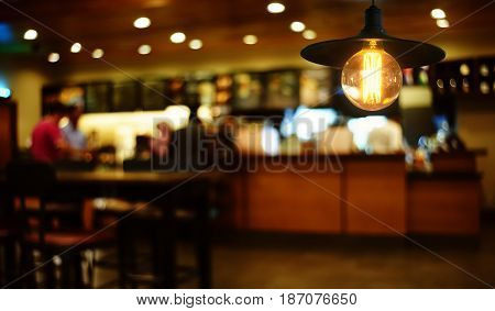 Hanging retro light lamp decor glowing in out of focus restaurant interior background .