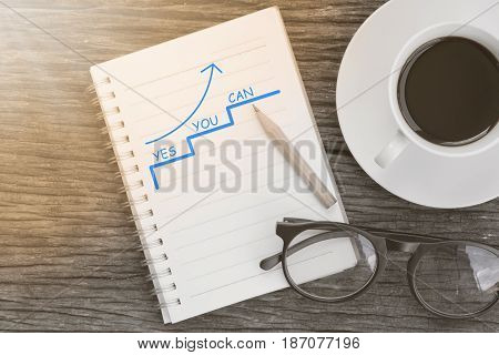 arrow pointing up with Yes You Can - Motivation Business Concept message on notebook with glasses pencil and coffee cup on wooden table.