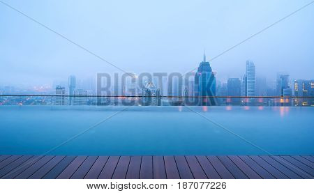 Swimming pool on roof top with beautiful city skyline viewearly morning with mist kuala lumpur malaysia.