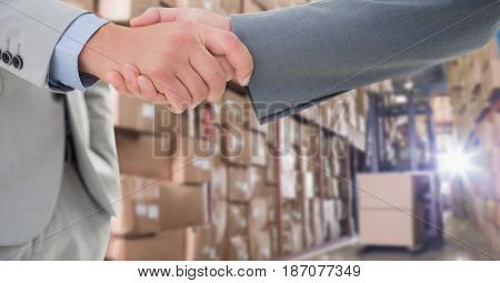 Digital composite of Cropped image of businessmen doing handshake in warehouse