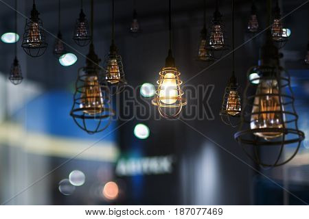Hanging retro light lamp decor glowing in out of focus office interior background .