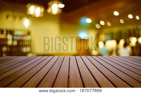 Wooden perspective brown empty table in front of coffe shop interior with bokeh blur background .