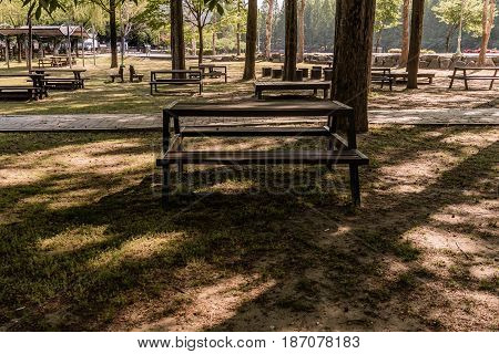 Wooden picnic tables shaded by trees in a wooded public park in South Korea