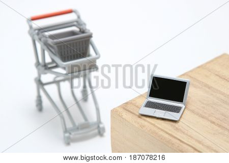 Miniature laptop with small shopping cart on white background. On line shopping concept.