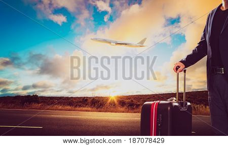 Business man with traveling luggage standing against landscape scene and passenger jet plane flying over sky .