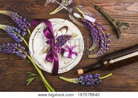 Tableware And Silverware With Violet Lupins On The Wooden Background