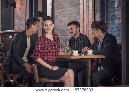woman looking to the camera small group of people sitting table drinking coffee coffee shop indoors