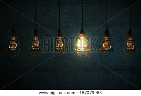 Hanging retro light bulbs decor on dark blue cement background with one isolated glowing .
