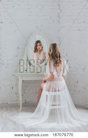 Gentle beautiful young girl in elegant lingerie in front of the mirror sees his reflection.